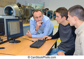 Two students using computer, teacher supervising