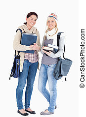 Two students with books prepared for winter - Two cute...