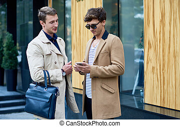 Two Stylish Men Chatting Outdoors