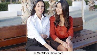 Two stylish woman sitting chatting outdoors
