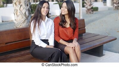 Two stylish woman sitting chatting outdoors