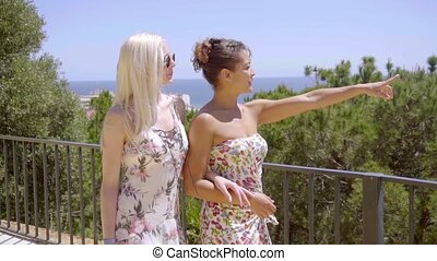 Two stylish woman walking on an outdoor patio - Two stylish...