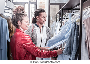 Two stylish women coming to new shopping mall looking at nice dresses