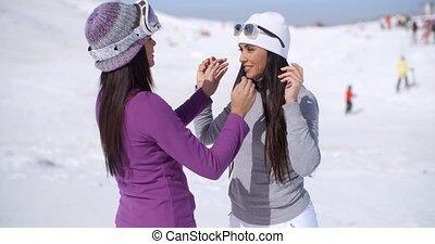 Two stylish young woman chatting at a ski resort