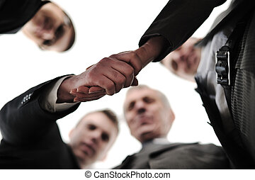 Two successful businessman shaking hands at front of corporate team in office