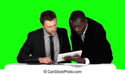 Two successful businessman sit down at the negotiating table in the office and working at his laptop. Green screen.