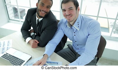 Two successful businessman smiling and showing his thumb up