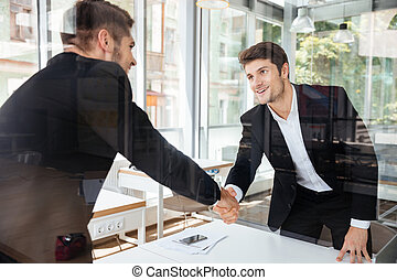Two successful businessmen standing and shaking hands on business meeting