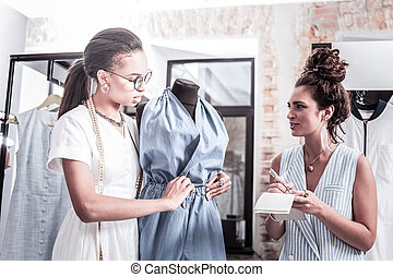 Two successful women being famous designers discussing their new collection