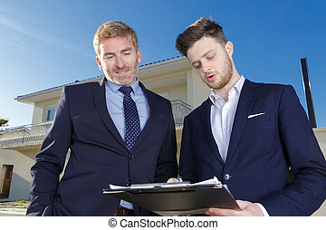 two suited men looking at clipboard outside of property