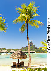 Two sunlounger chairs under a thatched parasol on a sand beach with a view on the lagoon and Mount Otemanu on the tropical island of Bora Bora, near Tahiti, in French Polynesia.