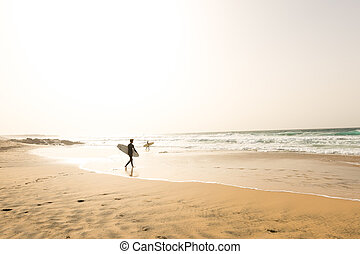 Two surfers walking to waves on an empty beach
