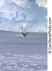 two surfers windsurfing in a storm