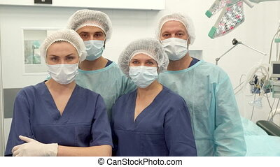 Two surgeons and two nurses pose at the surgery room