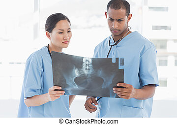 Two surgeons examining x-ray in a bright hospital