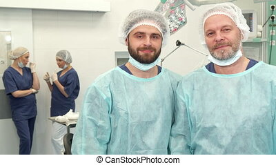 Two surgeons pose at the surgery room - Two caucasian...