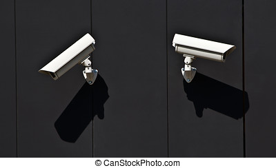 two surveillance cameras on the wall of a public building