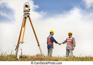 two Surveyor engineers handshaking on the field
