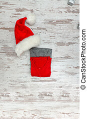 Two sweaters and santa hat on a wooden background. Fashionable concept