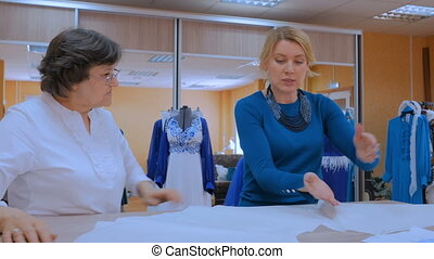 Two tailors discussing pattern of new dress - Two...
