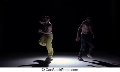 Two talanted dancers dance breakdance and turning around on black, shadow, slow motion