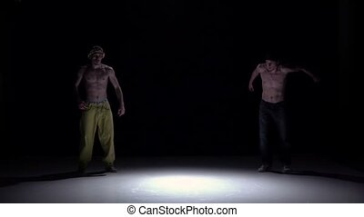 Two talanted dancers performing and continue dance breakdance on black, shadow, slow motion