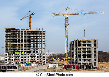 Two tall buildings under construction with cranes against blue sky.