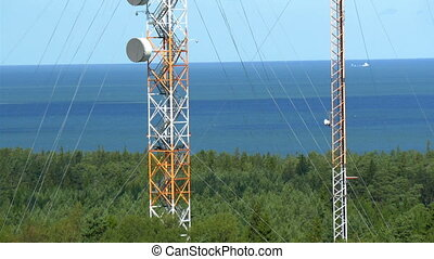 Two tall telecommunication towers in the middle of the field