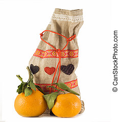 two tangerines with a green branch. On a white background close-up. Gift bag.