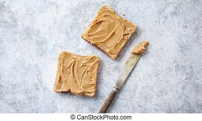 Two tasty peanut butter toasts placed on stone table. Knife...