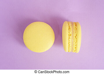 Two tasty yellow macarons on the purple background.