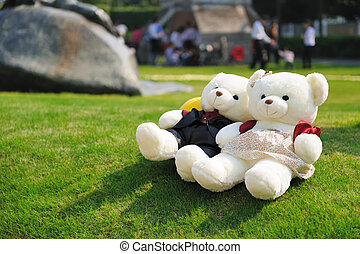 Two teddy bears lying on the lawn
