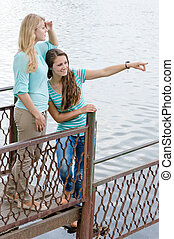 Two Teen Girl Friends looking over river on summer day
