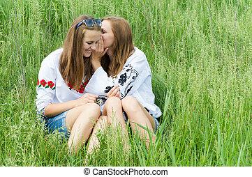 Two teen girl friends sharing secret