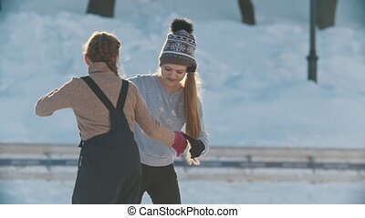 Two teen girlfriends learning to skate and having fun, youth...