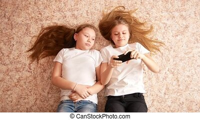 Two teen girls lying on the floor, laughing and making selfie the phone, their hair spread over the floor