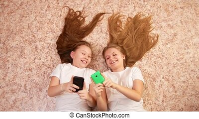 Two teen girls lying on the floor, use and typing on the...