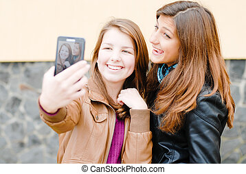Two teen girls taking picture of themselves using tablet pc...