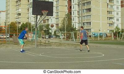 Two teenage friends practicing basketball skills