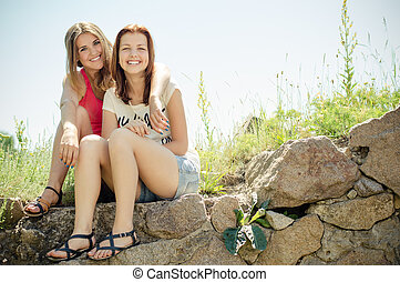 Two teenage girl friends having fun outdoors on summer day