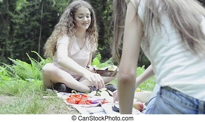 Two teenage girls camping and cooking. - Two teenage girls...