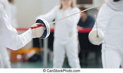Two teenage girls doing fencing in the gym