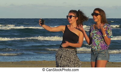 Two teenage girls enjoying a beautiful summer day and having video call on smart phone