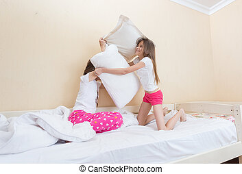 Two teenage girls in pajamas fighting with pillows