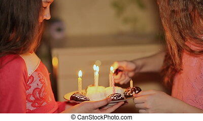 Two teenage girls lighting candles on birthday. Cake with candles close-up.