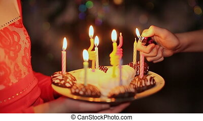 Two teenage girls lighting candles on birthday. Cake with candles close-up
