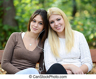 Two teenage girls listening to music outdoors