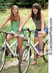 Two teenage girls riding bikes in countryside