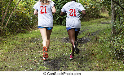 Two teenage girls running in the woods