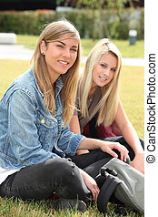 Two teenage girls sitting in a park